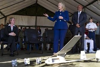 Hillary Clinton avec le ministre de la défense ougandais Jeje Odongo devant un drone miniature américain utilisé par l'armée ougandaise pour combattre les militants terroristes Al Shebab en Somalie
