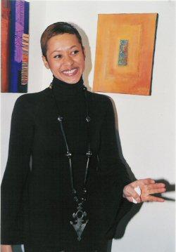 """Anne Yoro devant deux de ses tableaux, dont en Orange """"La porte des Initiés"""""""