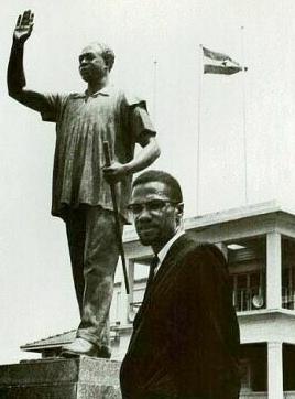Malcolm X au Ghana. A l'arrière plan, une statue de Kwame Nkrumah