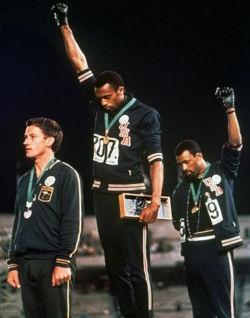 Tommie Smith (au centre) et John Carlos (à droite) levant leurs poings durant les JO de Mexico 1968